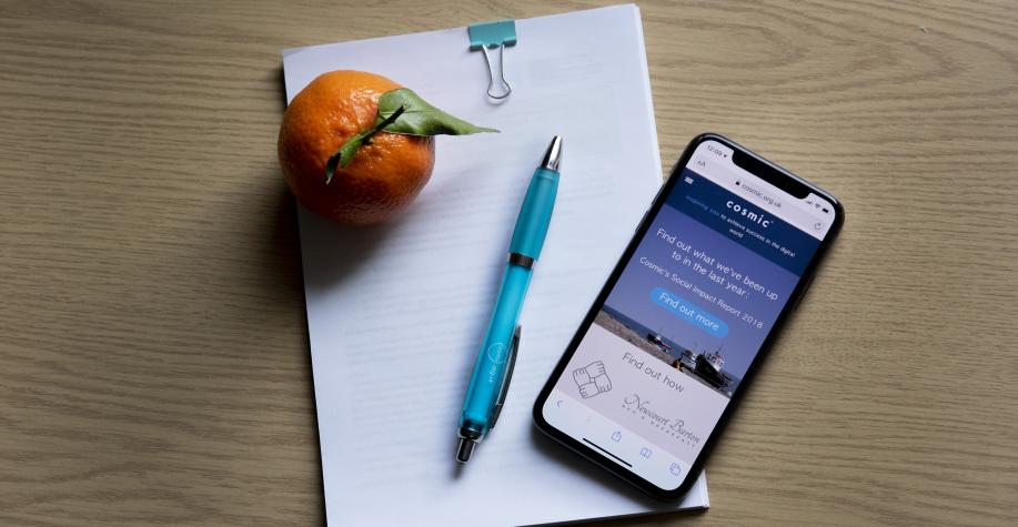 Notebook with a phone, pen and an orange sat on top.