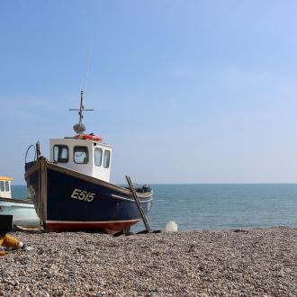 Person sitting on a pebble beach with a laptop next to some moored fishing boats